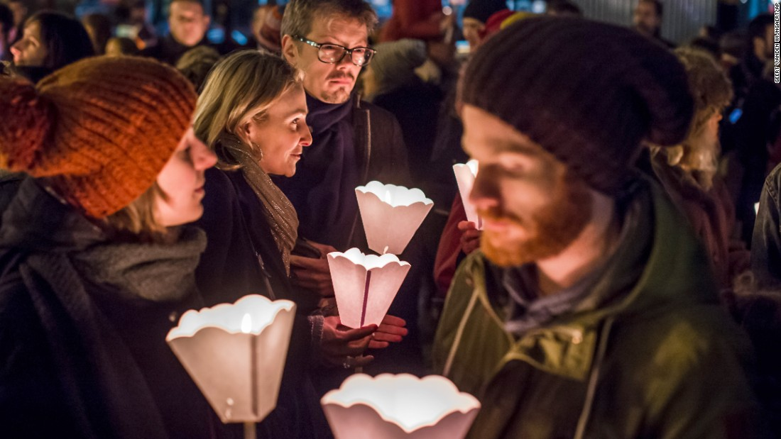 People in Brussels, Belgium, hold candles during a vigil on January 7.