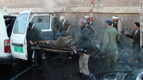 Yemeni security forces and emergency personnel carry a body on a stretcher at the site of a car bomb explosion outside a police academy in the capital Sanaa on January 7, 2015.