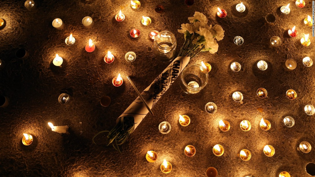 Flowers are placed at a candlelight vigil near the French Embassy in Tunis, Tunisia, on January 7.