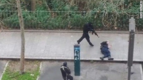 Masked gunmen run toward a victim in Paris on January 7.