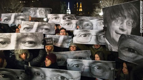 Mourners hold signs depicting victim's eyes during a rally in support of Charlie Hebdo, a French satirical weekly newspaper that fell victim to an terrorist attack, Wednesday, Jan. 7, 2015, at Union Square in New York. French officials say 12 people were killed when masked gunmen stormed the Paris offices of the periodical that had caricatured the Prophet Muhammad. (AP Photo/John Minchillo)