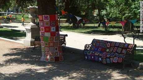 A yarn-bombed tree and bench add color to a park in central Santiago.