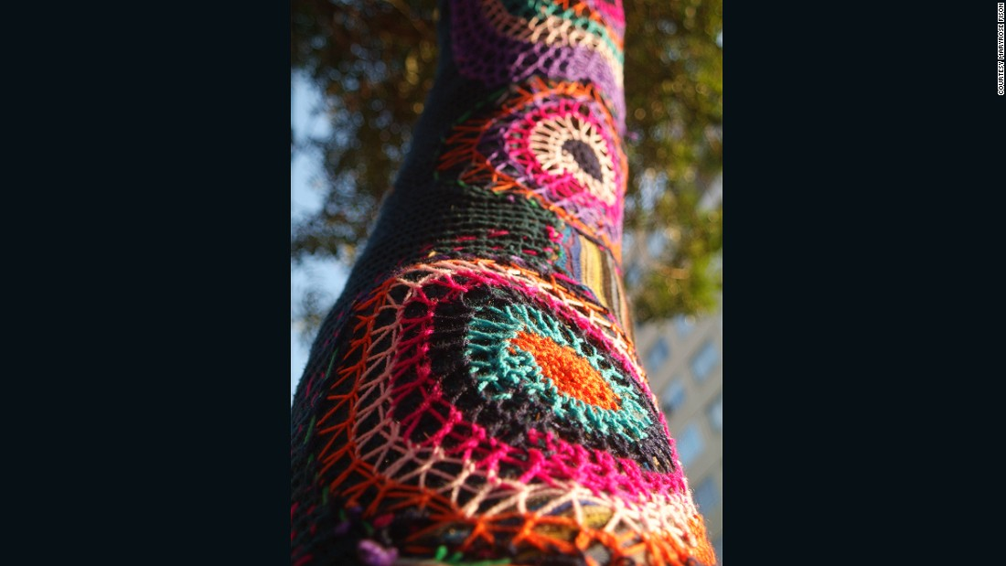 A yarn-bombed tree stands on a street in Barrio Bellavista.