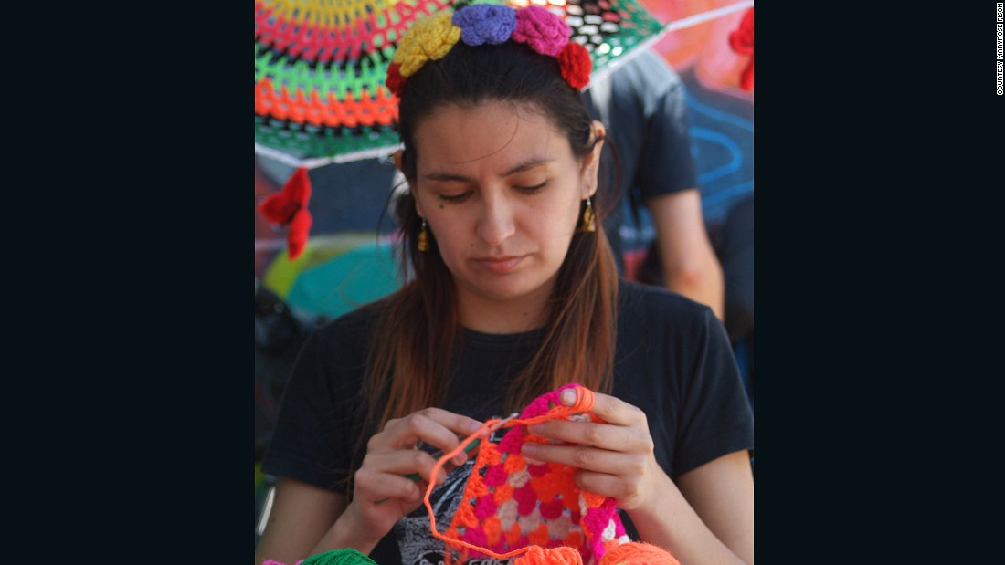 Claudia Araya Zuñiga, the founder of Santiago-based yarn-bombing group Lanaattack (Wool Attack) crochets a covering for a bicycle saddle at an open-air intervention in Barrio Italia, Santiago.