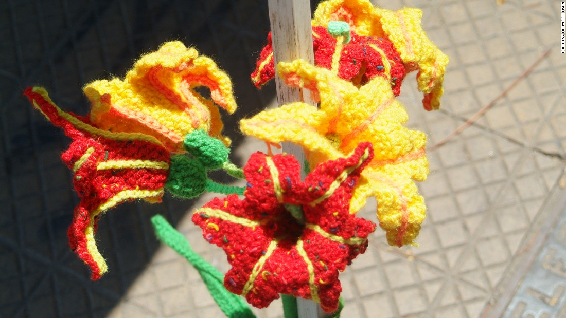 Crocheted lilies surround a tent pole at a yarn-bombing intervention in Barrio Italia.
