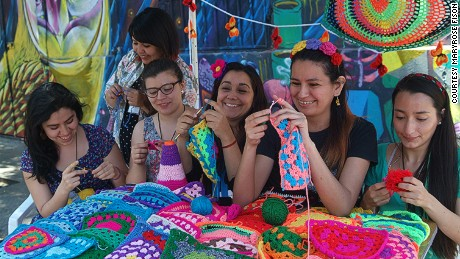 Members of Santiago-based yarn-bombing group Lanaattack (Wool Attack) crochet covers for bicycle saddles at an open air intervention in Barrio Italia, Santiago.