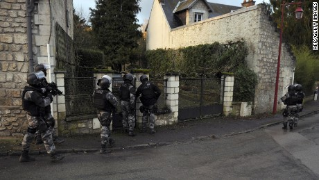 Members of the GIPN and RAID, French police special forces, walk in Corcy, northern France, on January 8, 2015 carry out searches as part of an investigation into a deadly attack the day before by armed gunmen on the Paris offices of French satirical weekly Charlie Hebdo. A huge manhunt for two brothers suspected of massacring 12 people in an Islamist attack at a satirical French weekly zeroed in on a northern town on January 8 after the discovery of one of the getaway cars. As thousands of police tightened their net, the country marked a rare national day of mourning for January 7's bloodbath at Charlie Hebdo magazine in Paris, the worst terrorist attack in France for half a century. AFP PHOTO / FRANCOIS LO PRESTIFRANCOIS LO PRESTI/AFP/Getty Images
