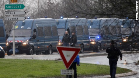 Police vans are lined up in Dammartin-en-Goele, northeast Paris, as part of an operation to seize two heavily armed suspects, Friday, Jan. 9, 2015. French security forces swarmed a small industrial town northeast of Paris Friday in an operation to capture a pair of heavily armed suspects in the deadly storming of a satirical newspaper. Shots were fired as the brothers stole a car in the early morning hours, said a French security official, who could not immediately confirm reports of hostages taken or deaths later in the day in the town of Dammartin-en-Goele, about 40 kilometers (25 miles) northeast of Paris.
