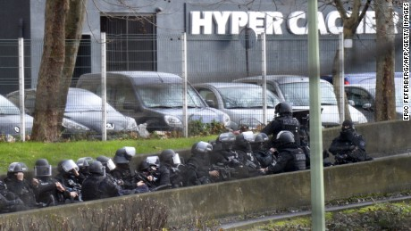 A photo taken on January 9, 2015 shows members of the French police forces taking position by the kosher grocery store in Saint-Mande, near Porte de Vincennes, eastern Paris, where at least one person was injured when a gunman opened fire at the kosher grocery store and took at least five people hostage, sources told AFP. The attacker was suspected of being the same gunman who killed a policewoman in a shooting in Montrouge in southern Paris on January 8. AFP PHOTO / ERIC FEFERBERG        (Photo credit should read ERIC FEFERBERG/AFP/Getty Images)