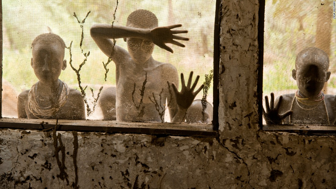 Children from Kara tribe look through screened windows.