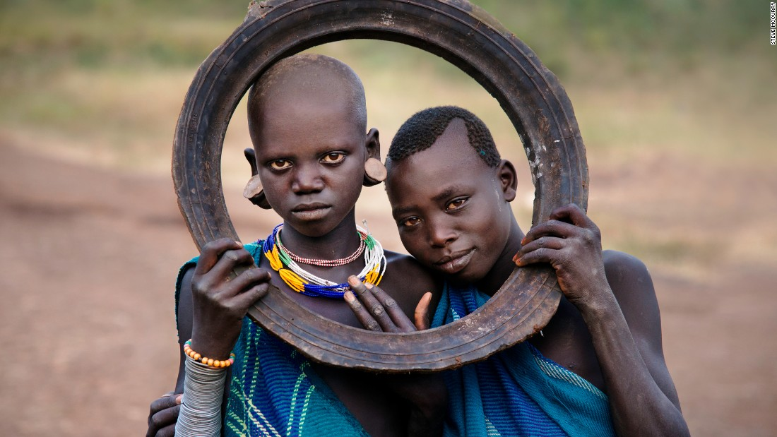 Two girls holding a tattered tire.