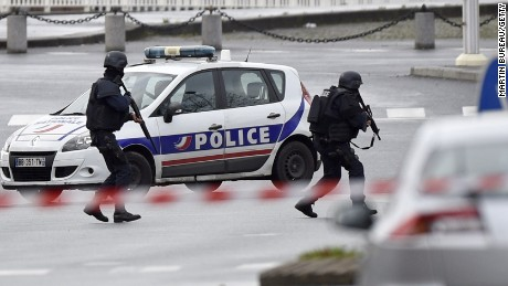 Caption:Police forces gather together at Porte de Vincennes, east of Paris, after at least one person was injured when a gunman opened fire at a kosher grocery store on January 9, 2015 and took at least five people hostage, sources told AFP. The attacker was suspected of being the same gunman who killed a policewoman in a shooting in Montrouge in southern Paris on January 8. AFP PHOTO / MARTIN BUREAU (Photo credit should read MARTIN BUREAU/AFP/Getty Images)