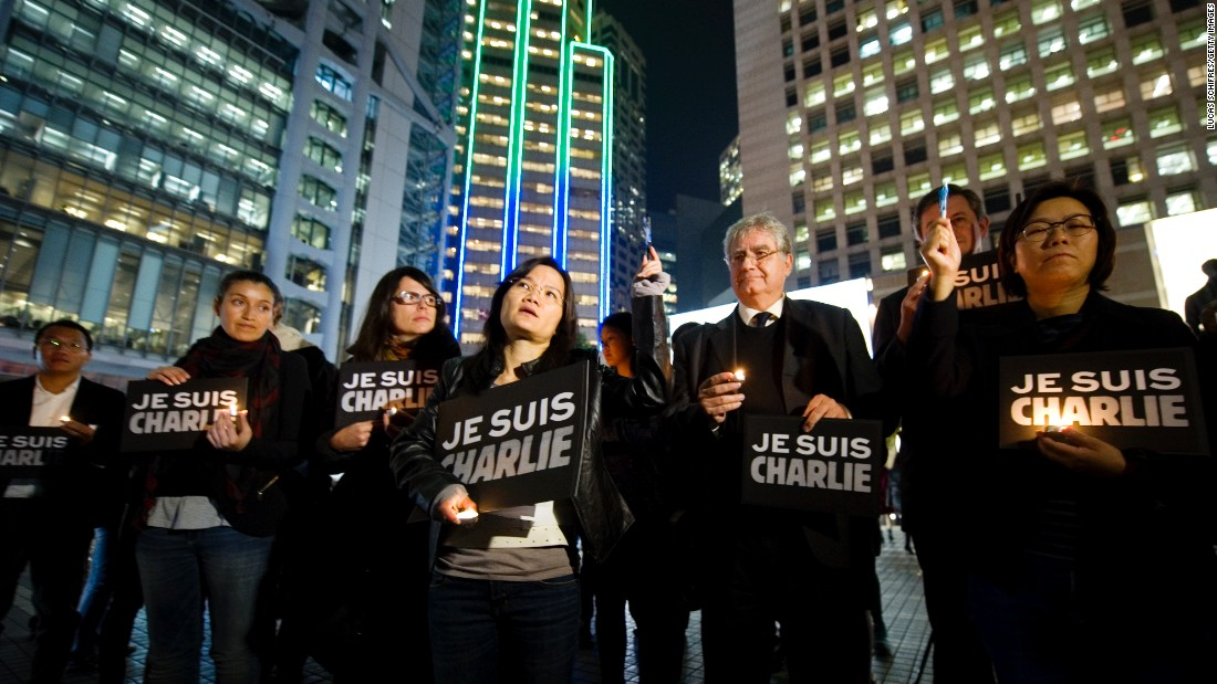 "Journalists and other people in Hong Kong hold up pens and hold signs that say ""Je suis Charlie"" (I am Charlie) during a vigil on January 9."