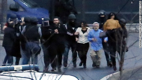 French police special forces evacuate hostages after launching the assault at a kosher grocery store in Porte de Vincennes in eastern Paris.