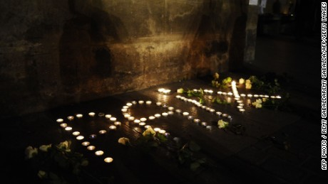 "Lit candles forming the word ""peace"" in French are layed outside the Capitole building in Toulouse, southern France, on January 9, 2015 during a gathering to pay tribute to the victims of a deadly attack two days prior on the Paris headquarters of French satirical weekly Charlie Hebdo. French elite forces stormed two hostage sites on January 9, killing the brothers behind the Charlie Hebdo massacre and a jihadist accomplice in a fiery end that also claimed the lives of four hostages. The killings brought a dramatic close to three days of terror and high tension that began on January 7 when the two heavily armed Kouachi brothers burst into the satirical magazine's office and slaughtered some of France's best-loved cartoonists"