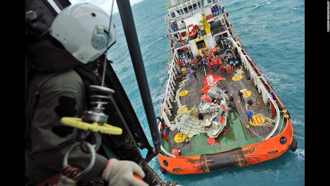A portion of the plane's tail section is seen on the deck of a rescue ship after it was recovered from the Java Sea on Saturday, January 10.