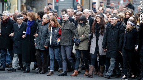 Cartoonist Renald Luzier, known as Luz, center with moustache, marches with other survivors of the Charlie Hebdo massacre as well as family members of victims.