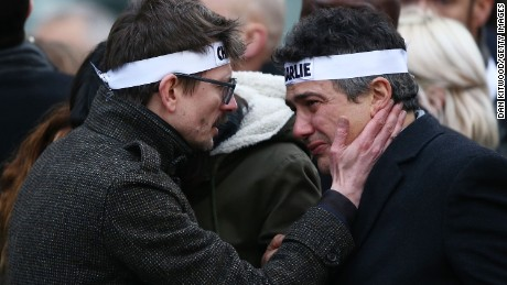 "Patrick Pelloux (right), a journalist at Charlie Hebdo, is embraced by Renald ""Luz"" Lucier (left), cartoonist at the magazine."
