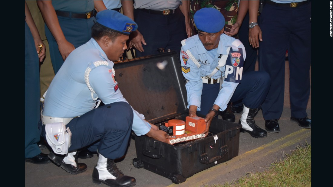 Indonesian officials remove the cockpit voice recorder from AirAsia Flight QZ8501 on Tuesday, January 13. Indonesian divers retrieved it from beneath the wreckage of the plane.