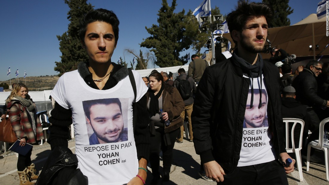 Mourners wearing t-shirts bearing the picture of a victim arrive at Givat Shaul cemetery in Jerusalem.<br />