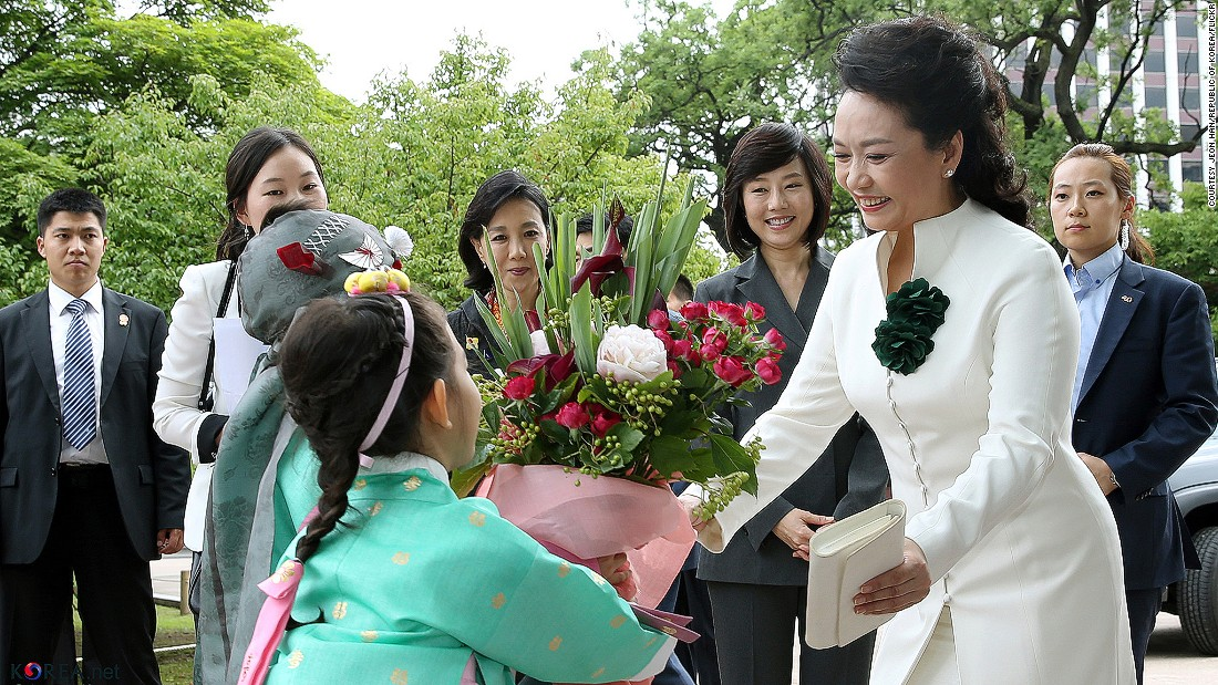 "Overseas shops visited by China's First Lady, Peng Liyuan, benefit from the ""Peng Liyuan phenomenon."" Some products she purchases see a three-fold increase in sales, according to reports."