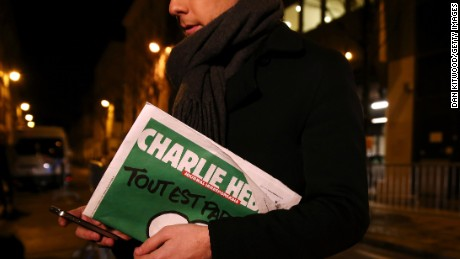 PARIS, FRANCE - JANUARY 13: A journalist holds an early copy of a Charlie Hebdo magazine while delivering a news report outside the offices of Liberation Newspaper Group on January 13, 2015 in Paris, France. Three million copies of the controversial magazine have been printed and are due to be released tomorrow, in the wake of last weeks terrorist attacks. (Photo by Dan Kitwood/Getty Images)