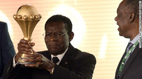 Equatorial Guinea President Teodoro Obiang Nguema (L) holds the CAN trophy as CAF President Issa Hayatou looks during the 2015 African Cup of Nations draw ceremony on December 3, 2014 in Malabo. The African Cup of Nations (CAN 2015) will be held in Equatorial Guinea from January 17, 2014 until February 8, 2014. AFP PHOTO / STEPHANE DE SAKUTIN