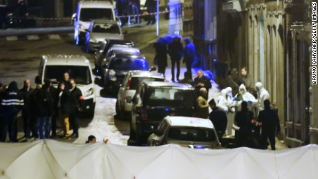 Policemen and forencic police work inside a marked out perimeter at the scene.