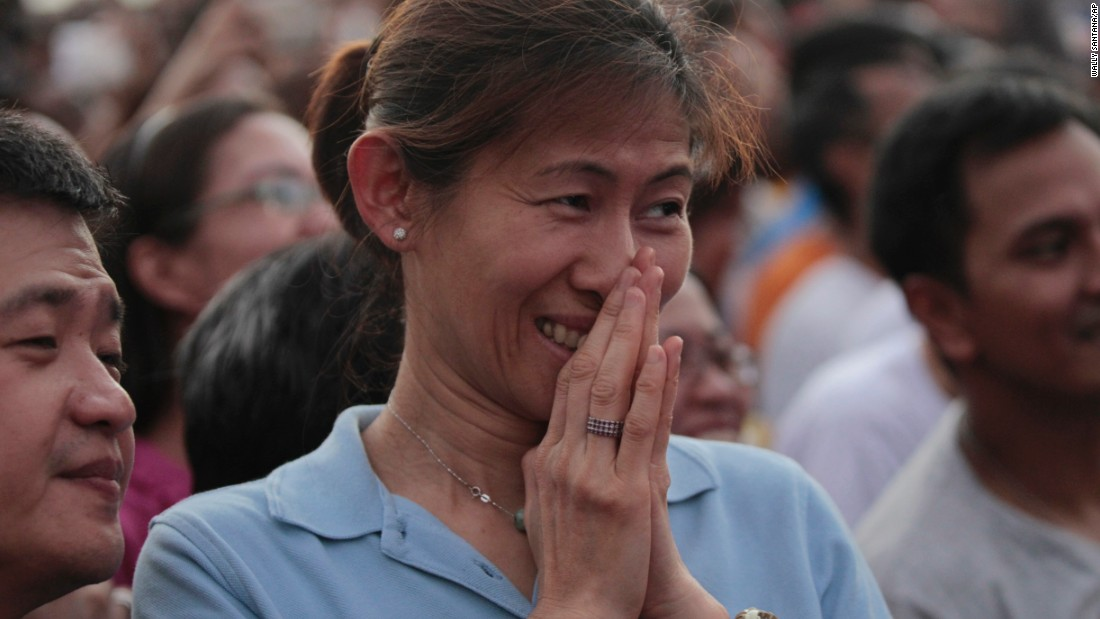 "The faithful react while watching a screen showing the arrival of Pope Francis in Manila, on January 15. Giant billboards with an official red and blue ""Pope logo"" adorn many of Manila's buildings, while curbside vendors sell images of his smiling face on everything from stamps and towels to fans and key chains."