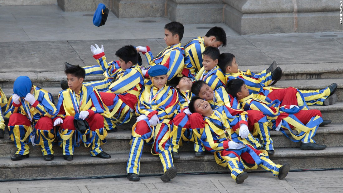 Boys dressed as the Swiss Guard rest January 16 as they wait for Pope Francis' arrival at the Cathedral Basilica of the Immaculate Conception in Manila.