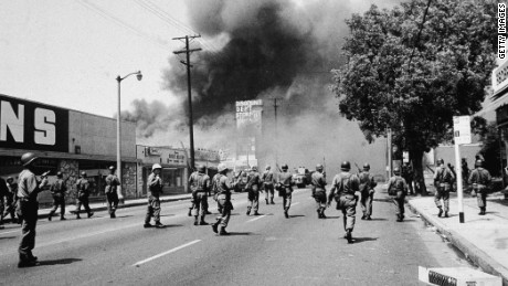 Armed National Guardsmen march toward smoke on the horizon during the street fires of the Watts riots, Los Angeles, California, August 1965. (Photo by Hulton Archive/Getty Images)