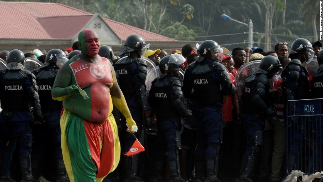 Fans arriving for the the Group B match between Zambia and the Democratic Republic of Congo in Ebebiyin add some patriotic color to the lines of uniformed police.