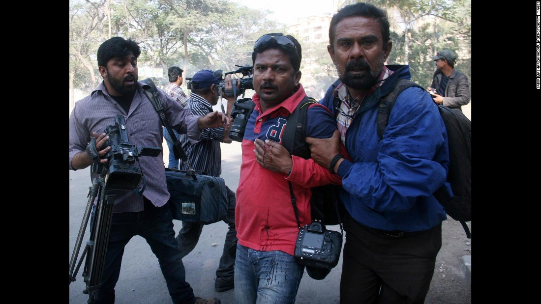 Agence France Presse photographer Asif Hassan, center, is helped after being shot during protests outside the French Consulate in Karachi on January 16.