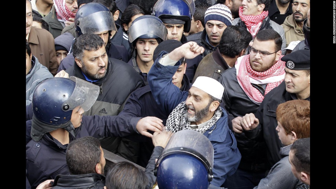 Members of Jordanian security services surround a protester in Amman on Thursday, January 15.