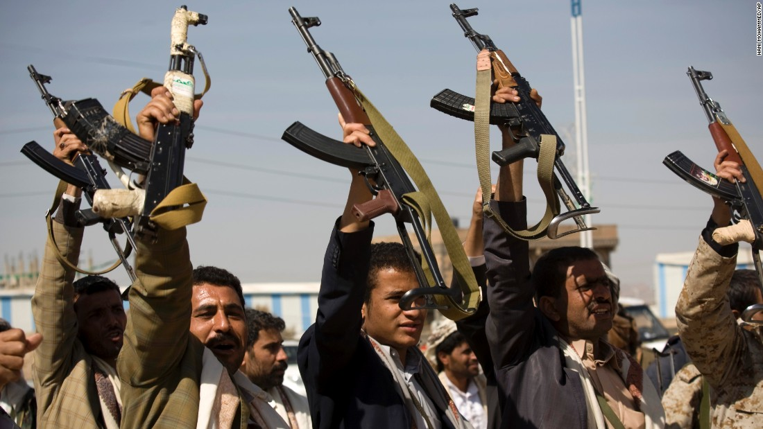 Houthi men raise their weapons during clashes near the presidential palace on Monday, January 19.