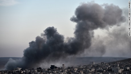 Smoke rises after an airstrike from US-led coalition in the city of Kobane, also known as Ain al-Arab, seen from the southeastern border village of Mursitpinar, Sanliurfa province, on November 9, 2014. AFP PHOTO / ARIS MESSINIS (Photo credit should read ARIS MESSINIS/AFP/Getty Images)