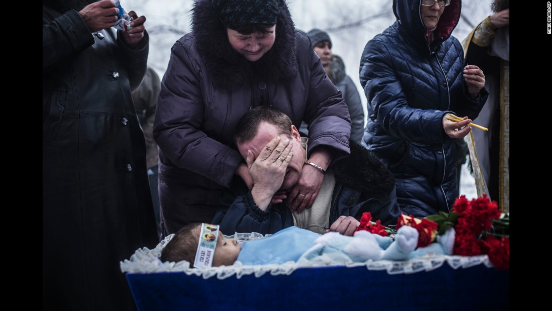 Vladimir Bovrichev cries next to the body of his 4-year-old son, Artiam, during Artiam's funeral on the outskirts of Donetsk on Tuesday, January 20. The boy was killed during a Ukrainian artillery strike.