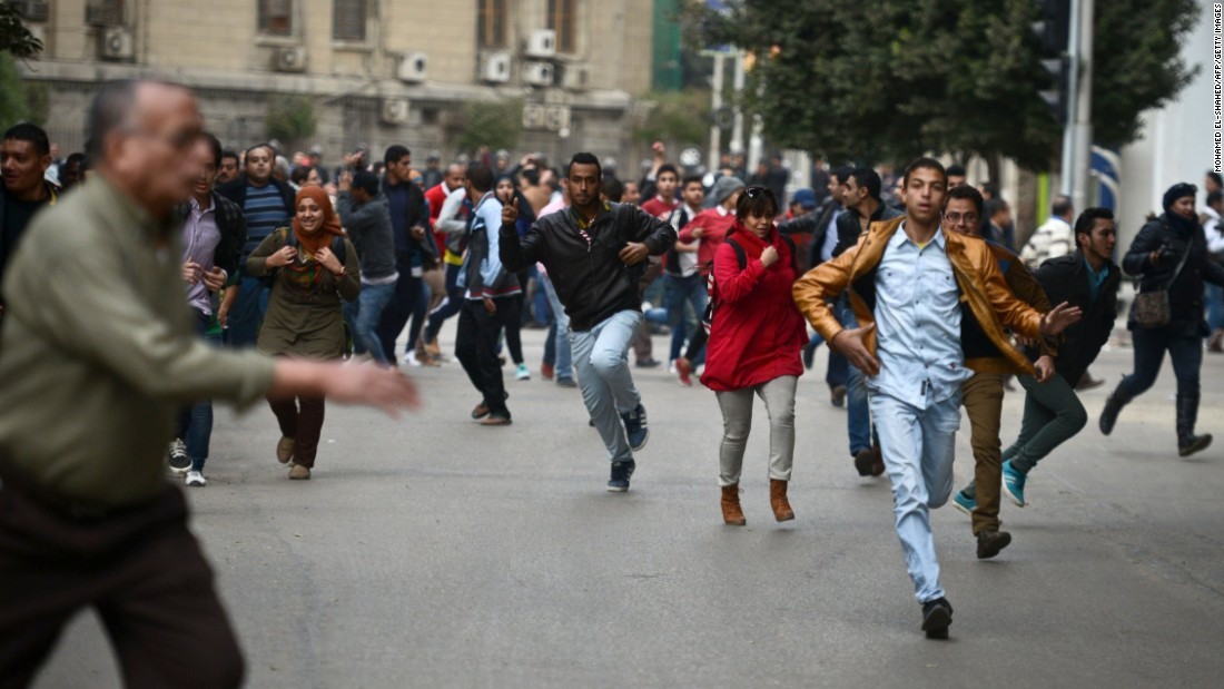 Opponents of Egyptian President Abdel Fattah el-Sisi run for cover during clashes with pro-government demonstrators on January 25 in Cairo.