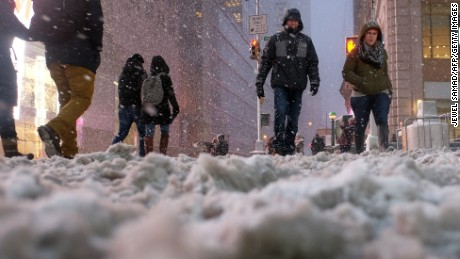 "People cross a street covered in snow in New York's Times Square during a snow storm on January 26, 2015. A winter storm pounded the northeastern United US on January 26 hitting tens of millions of people and forcing the rare cancelation of Broadway shows in an ""historic"" New York blizzard. Winter Storm Juno is expected to dump up to three feet (around a meter) of snow in parts of the northeast, with the worst affected areas likely to be New England, particularly Connecticut and Massachusetts. More than 6,560 flights on Monday and Tuesday were cancelled, the New York city transit system was to shut at 11pm and road travel made a criminal offense in 13 counties of New York state. AFP PHOTO/JEWEL SAMAD        (Photo credit should read JEWEL SAMAD/AFP/Getty Images)"