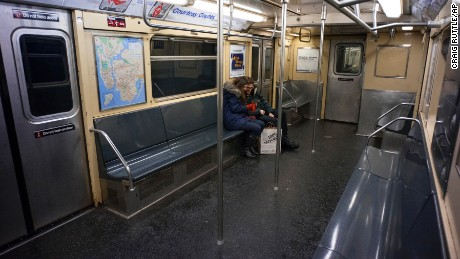 Two passengers ride a subway car in New York on January 26.