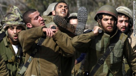 Israeli soldiers carry an injured soldier Wednesday on the border with Lebanon.