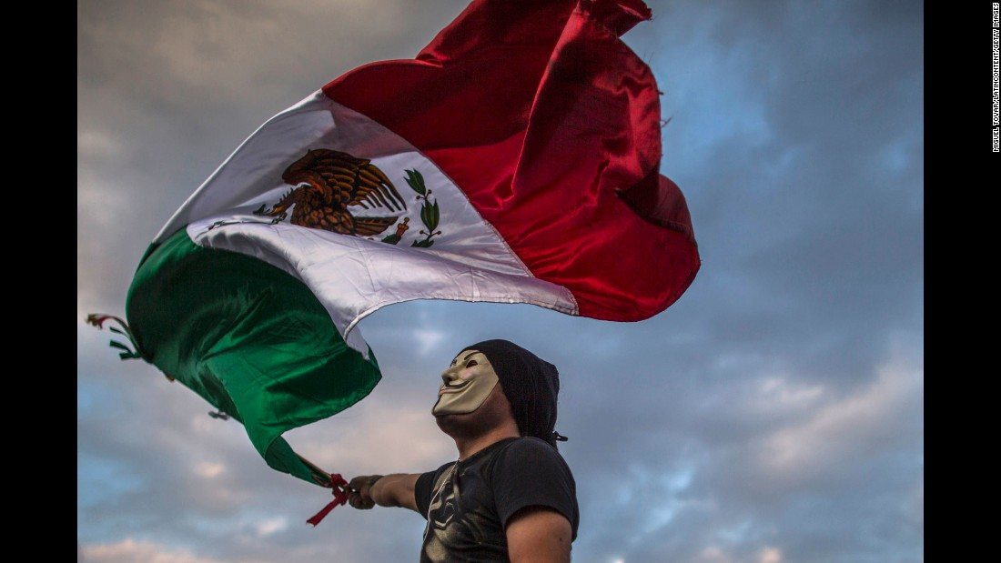 A masked protester waves a Mexican national flag during protests in Mexico City on January 26.