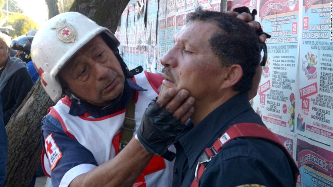 A firefighter who had been working on the wreckage is examined by a Red Cross paramedic.