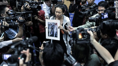 "A relative (C) of a passenger of the missing Malaysia Airlines flight MH370 holds a picture of Malaysian Prime Minister Najib Razak with the writing ""Please bring back my husband"" after the Department of Civil Aviation (DCA) decided to cancel a press conference in Putrajaya on January 29, 2015. Malaysia's government said it would make a statement on January 29 regarding missing Malaysia Airlines flight MH370, as rumours swirled the plane was to be formally declared ""lost"". AFP PHOTOSTR/AFP/Getty Images"