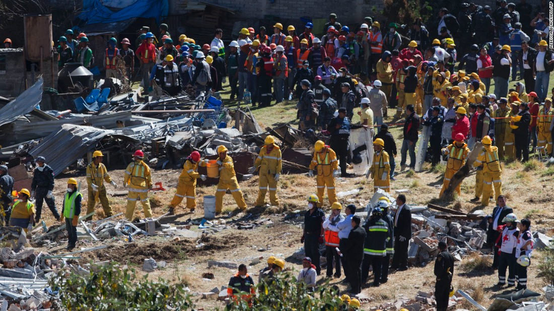 Rescue workers form a human chain as they clear wreckage following the explosion.