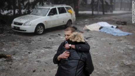 A rebel comforts a wife of a killed civilian in shelling in Donetsk, eastern Ukraine, Friday, Jan. 30, 2015. Artillery fire in the rebel stronghold of Donetsk killed at least 12 civilians on Friday afternoon, the city hall in the rebel stronghold said, as fighting intensifies between pro-Russia separatists and government troops. (AP Photo/Vadim Braydov)
