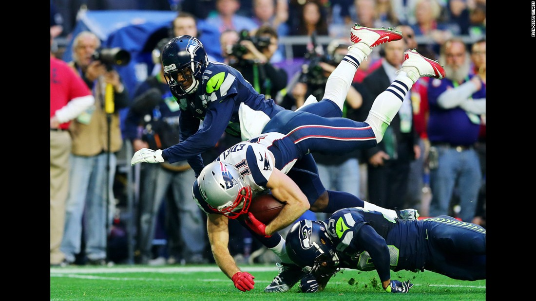 Edelman is tackled by two Seahawks during the first half.