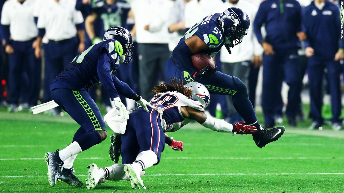 Seattle linebacker Bobby Wagner, right, runs the ball after intercepting Brady in the third quarter. The turnover set up Baldwin's touchdown drive.