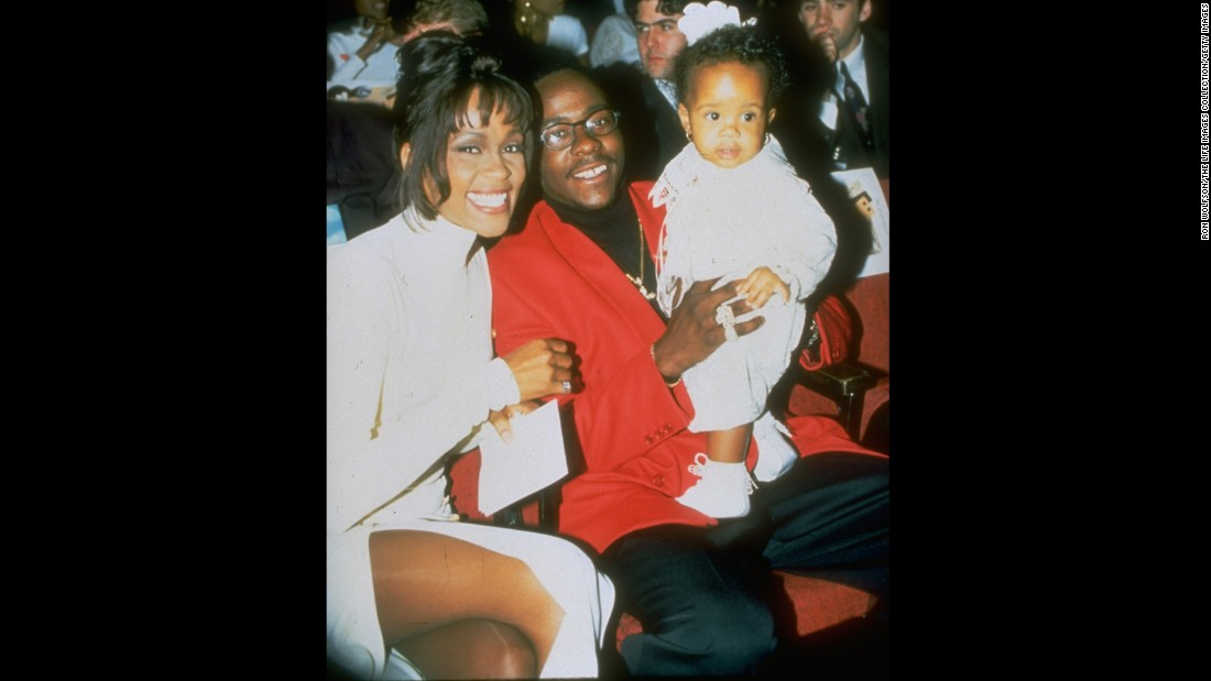In this undated photo, probably from 1993, Houston and her husband pose with their infant daughter.