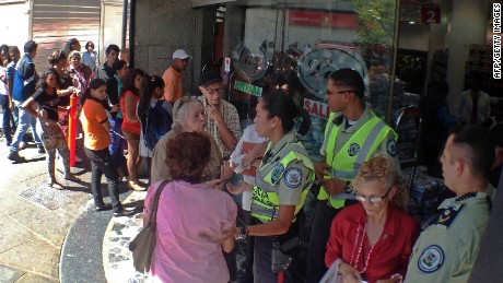 People queue outside a supermarket in Caracas on January 27, 2015.